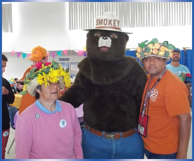 VTC individuals in party hats posing with Smokey the Bear at annual Spring Fling event
